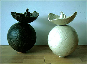 Photo of a black and a white sphere with another fragment of sphere above each one.