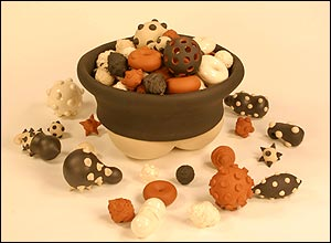 Photo of a ceramic bowl containing variously coloured ceramic shapes in brown, terracotta, cream and white.