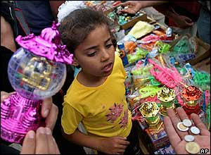 Palestinian girl looks on as her father buys toys in Rafah refugee camp, southern Gaza Strip