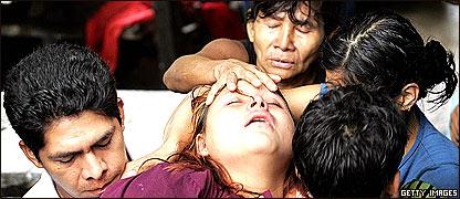 Familiares intentan consolar a una mujer ante la pérdida de cinco integrantes de su familia en El Salvador.