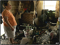 A woman surveys the damage to her home after the floods