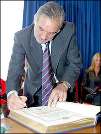 George Best signs a guest book as he is given the freedom of Castelreagh