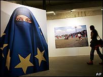 A visitor walks past a poster depicting a woman wearing a veil made from an EU flag
