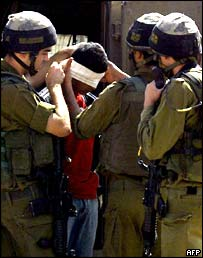 A Palestinian teenager is arrested by Israeli soldiers