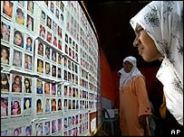 Women search the posters of missing children in Indonesia