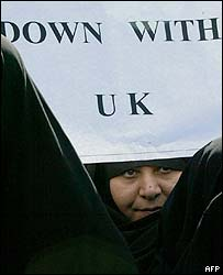 Hardline Iranian woman with an anti-British banner
