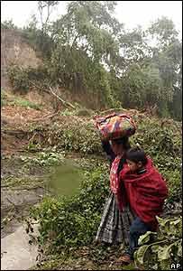 Habitantes de Los Encuentros, Guatemala, caminan por la inundada autopista interamericana