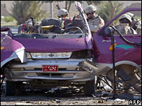 US soldiers inspect the minibus in Baghdad in which a suicide bomber blew himself up