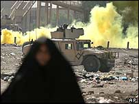 Iraqi woman standing in front of US army vehicle