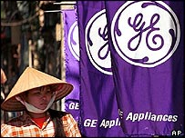 A Vietnamese woman passes signs for a GE store in Hanoi