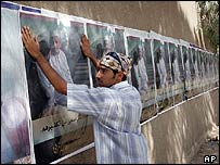 A man in Baghdad, Iraq, pastes up posters promoting the country's new constitution