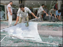 Employees clean up shattered glasses off at a clothing store across the street from the site where one of Saturday's bombs exploded in Kuta, Bali, Indonesia, Friday, Oct. 7, 2005.