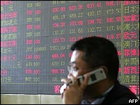 Chinese banker in front of a screen displaying foreign exchange prices