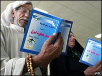 Elderly Iraqi man and woman read copies of constitution