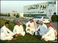 رجال سعوديون يجلسون بجوار لافتة انتخابية كبيرة في المنطقة الشرقية