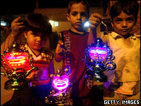 Palestinian children hold plastic lanterns in Rafah during Ramadan in the southern Gaza Strip