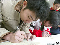 Students mark their voting papers at a polling station in Beijing Wednesday Dec. 10, 2003.