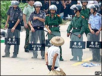 A villager walks past a row of riot police at Taishi village, in southern China's Guangdong province Monday Sept. 12, 2005