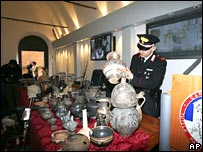 An Italian Carabinieri paramilitary police officer shows some artefacts recovered in an anti-art theft operation