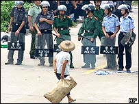 A villager walks past a row of riot police in Taishi, southern China