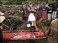 Brigadas de rescate llevan el cadáver de un niño en Panabaj, Guatemala