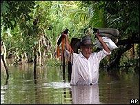 José Manuel Escobar camina por las calles inundadas El Mario 2, cerca de Las Aranas en El Salvador