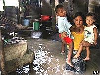 María Elena Cortez, con sus dos niños en brazos en su casa inundada en Las Aranas, El Salvador