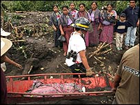Rescue workers carry the body of a child that found dead after a mudslide in Panabaj, Guatemala