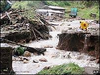 Brigadas de rescate intentan cruzar un puente en Tecpán, Guatemala