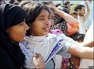 Women watch the rescue effort in Islamabad, Pakistan