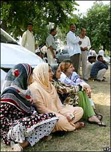 Office workers in Islamabad sit out the quake in a car park
