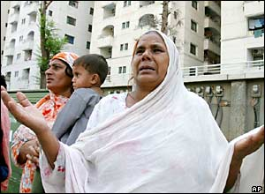 Women pray for those trapped under a collapsed tower block in Islamabad, Pakistan
