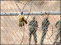 A glove hangs on the wire fence at the border