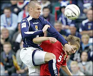 Scotland's Kenny Miller challenges Vladimir Korytko as he tries to get his team back into the game