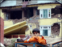 A boy stands in front of the ruins of a house in Indian-administered Kashmir