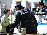 Beijing police stop a woman on Tiananmen Square to check her bags, 04 March 2005.