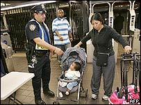 A policeman in New York City searches a woman with a child in a pushchair