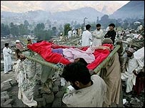 Villagers carry out an injured survivor from the rubble of Shaheen school in Balakot