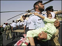 A Pakistani military officer at Chaklala air base in Rawalpindi carries a girl evacuated from Kashmir