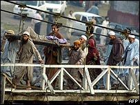 Villagers in Balakot, North-West Frontier Province, carry away an injured earthquake victim