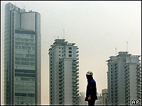 A construction worker stands near a newly built building in Shanghai, Jan 2005