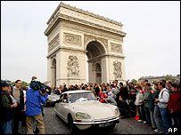 Citroen DS cars parade past the Arc de Triomphe in Paris