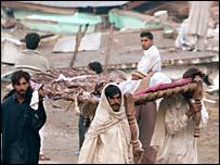 Villagers carry away a body in Balakot, Pakistan