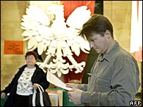 A man looks at his ballot in a polling station  in Warsaw with the white eagle, Poland's emblem, in the background