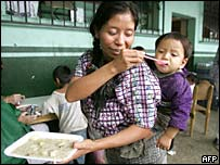 A woman feeds her child in a shelter at the Catholic church in Panabaj