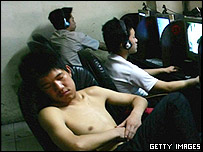 : Chinese youngsters sleep at an internet cafe on June 11, 2005 in Wuhan, Hubei Province of China.