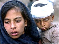 A Pakistani girl holds her injured brother