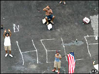 US citizens on rooftop with chalked message asking for help after Katrina.  Image: AP