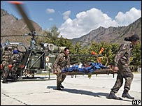 Indian army soldiers airlift an earthquake victim at Tangdar in Indian-administered Kashmir