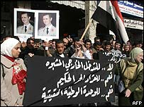 Syrians gather in front of the parliament holding pictures of Syrian President Bashar al-Assad